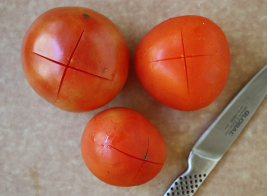 """How to peel fresh tomatoes: Slice a shallow """"X"""" on the bottom of each tomato // FoodNouveau.com"""