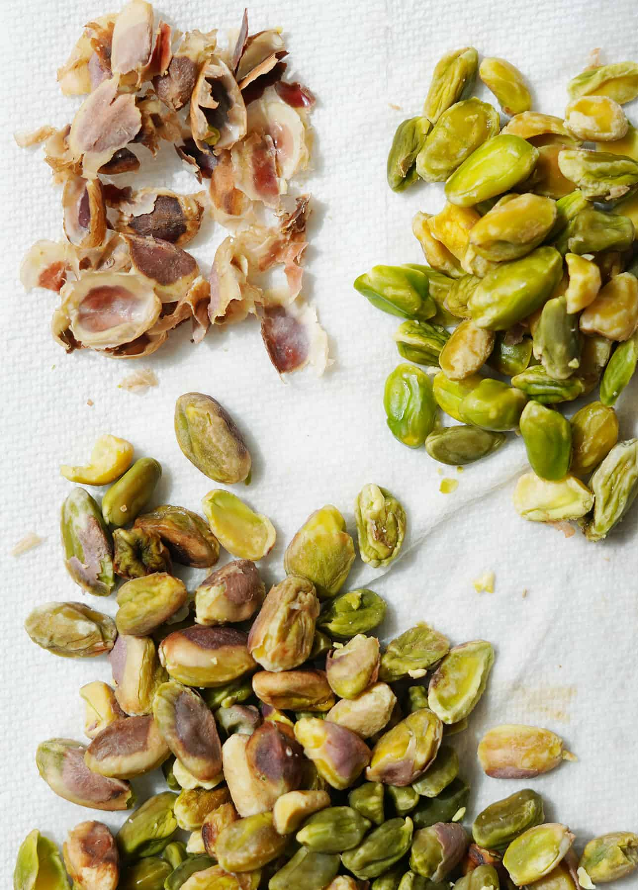 Peeling blanched pistachios to create a smoother, creamier pistachio semifreddo // FoodNouveau.com